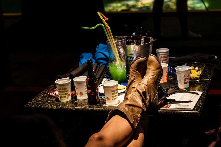 Jamie Tirrell rests her boots on a table at Top Golf during the Suits and Boots party on Saturday, Jan. 25, in Houston. (Michael Starghill Jr. / For the Houston Chronicle) Photo: Michael Starghill Jr. / For The Houston Chronicle