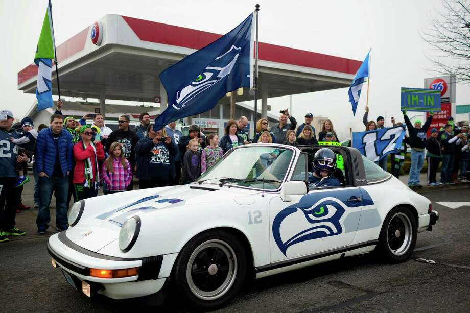 Kel Klink, in his vinyl-wrapped 1978 Porsche 911, rallies alongside thousands of diehard 12thMan fans who lined South 188th Street to see off the Seahawks team buses on their way to the airport en route to New York for Super Bowl XLVIII Sunday, Jan. 26, 2014, in SeaTac. Photo: JORDAN STEAD, SEATTLEPI.COM / SEATTLEPI.COM