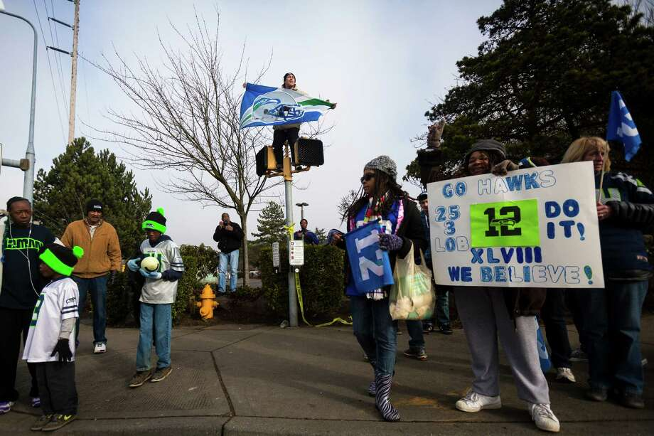 High above the crowd and perched on a crosswalk sign, Kristian Martinez, 22, rallied with thousands of diehard 12thMan fans on South 188th Street to see off the Seahawks team buses on their way to the airport en route to New York for Super Bowl XLVIII Sunday, Jan. 26, 2014, in SeaTac. Photo: JORDAN STEAD, SEATTLEPI.COM / SEATTLEPI.COM