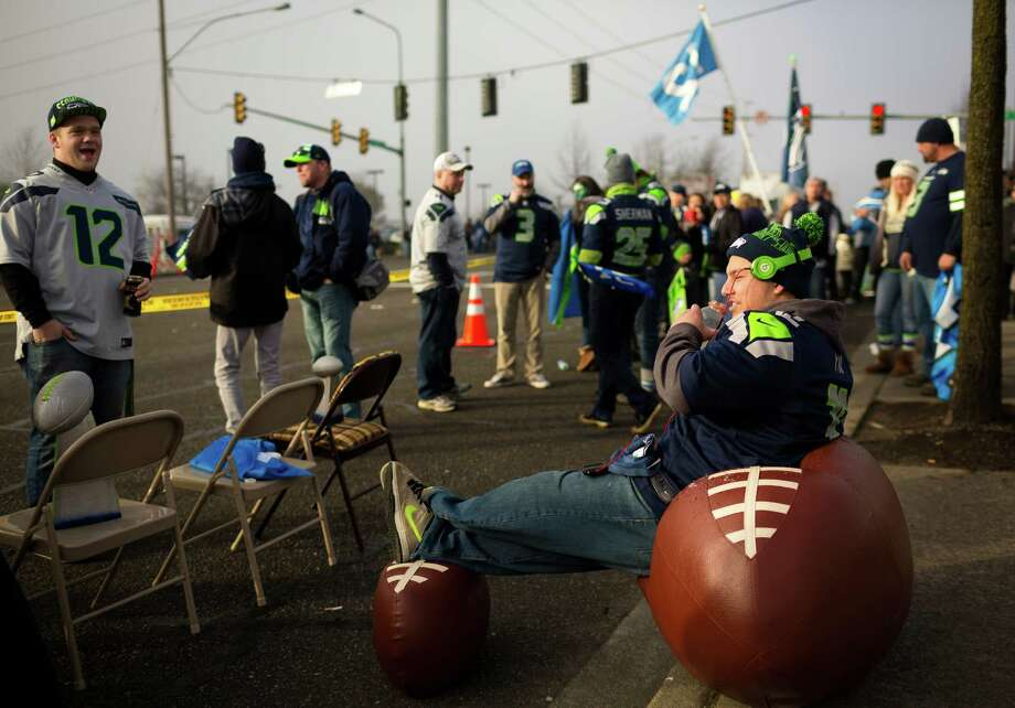 Jordan Salvatore, 23, right, in a football chair and ottoman, waits to see off the Seahawks team buses on their way to the airport en route to New York for Super Bowl XLVIII Sunday, Jan. 26, 2014, in SeaTac. Photo: JORDAN STEAD, SEATTLEPI.COM / SEATTLEPI.COM