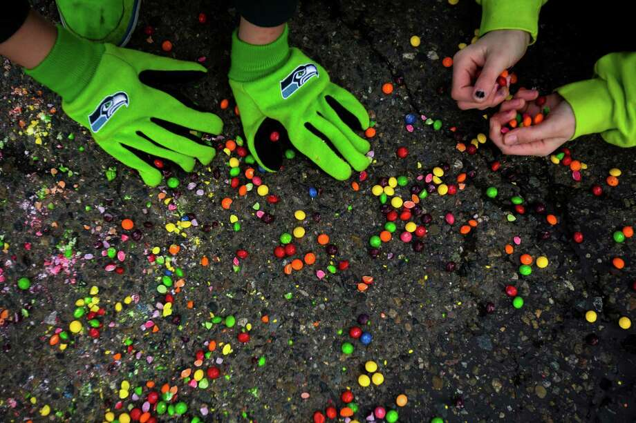 Children scoop up tossed Skittles on South 188th Street while seeing off the Seahawks team buses on their way to the airport en route to New York for Super Bowl XLVIII Sunday, Jan. 26, 2014, in SeaTac. Photo: JORDAN STEAD, SEATTLEPI.COM / SEATTLEPI.COM