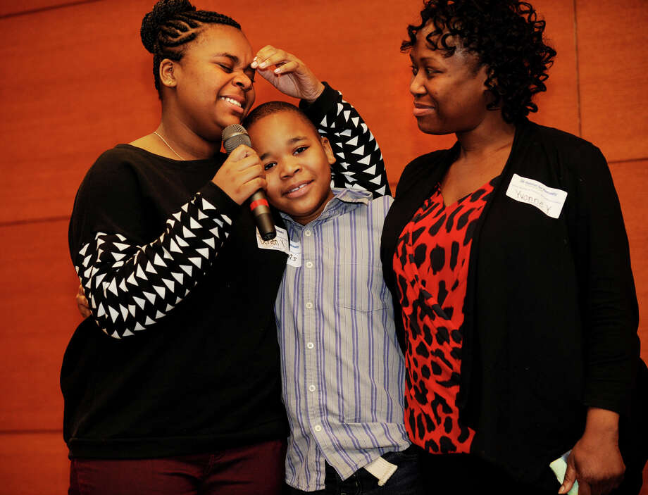 From left; Derien Young, 13, fights back tears as she, her brother, Marcquis Bender, 10, and mother, Yvonne Young, of Wilmot Avenue in Bridgeport, discuss their Habitat for Humanity experience as new 2013 homeowners at the charity's Annual Meeting & Volunteer Recognition Ceremony at Congregation B'Nai Israel in Bridgeport, Conn. on Sunady, January 26, 2014. Photo: Brian A. Pounds / Connecticut Post