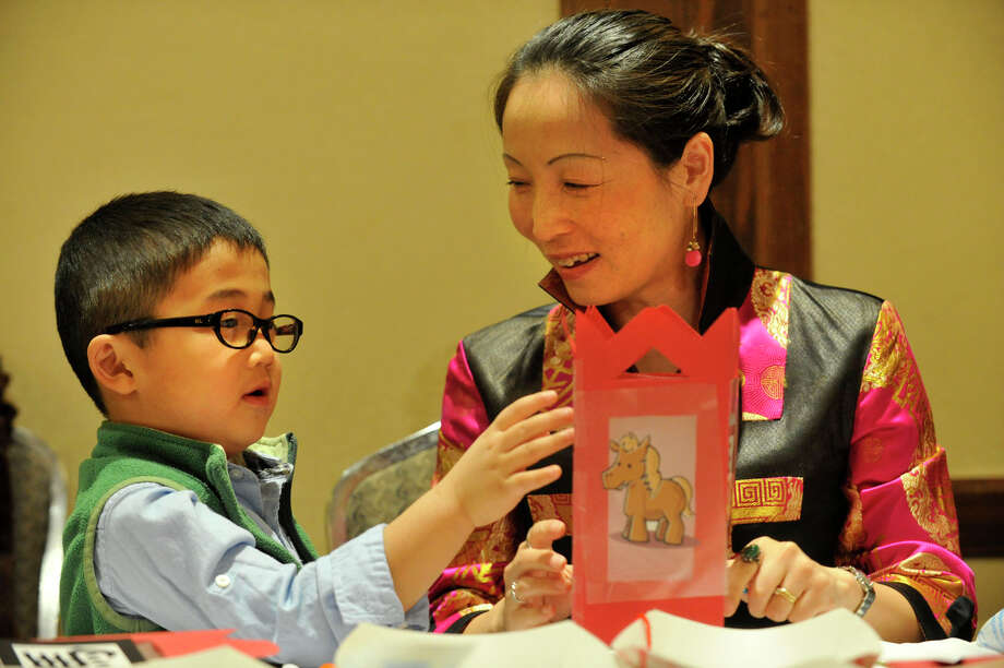 Chelsea Li and her son, William Kwong, construct a decorative lantern during the Chinese Language School of Connecticut's Chinese New Year Festival heralding the year of the horse at the Hilton Stamford Hotel in Stamford, Conn., on Sunday, Jan. 26, 2014. Photo: Jason Rearick / Stamford Advocate