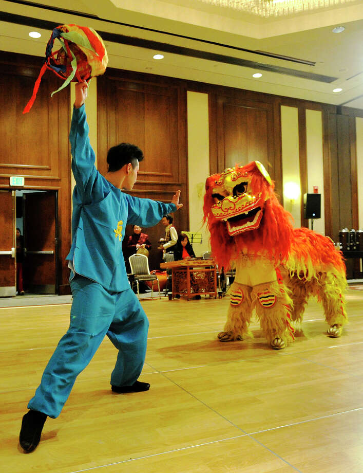 Li Qing Feng, left, dances the Northern Lion Dance with the lion played by Sun Shi Kui, in the head section, and Zhao Gang, in the tail section, during the Chinese Language School of Connecticut's Chinese New Year Festival heralding the year of the horse at the Hilton Stamford Hotel in Stamford, Conn., on Sunday, Jan. 26, 2014. Photo: Jason Rearick / Stamford Advocate