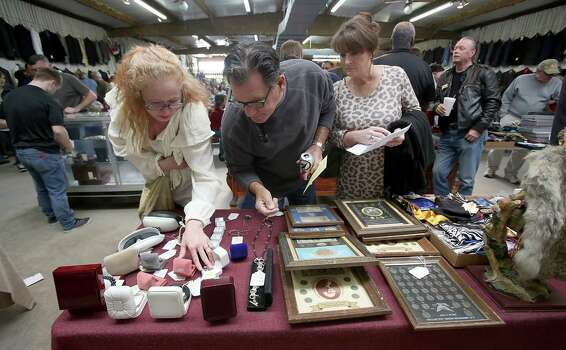 Melissa Pavey from Channelview, left, and Gary and Becky Gray from The Woodlands look at cufflinks, lighters, pins and other jewelry before the start of the fourth auction Sunday. Photo: Thomas B. Shea, The Houston Chronicle / © 2014 Thomas B. Shea