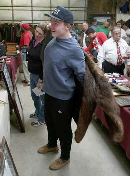 Cody Rich, from Sugar Land, tries on a beaver fur coat before the start of the fourth sale at Webster's Auction Palace in Houston. Photo: Thomas B. Shea, The Houston Chronicle / © 2014 Thomas B. Shea