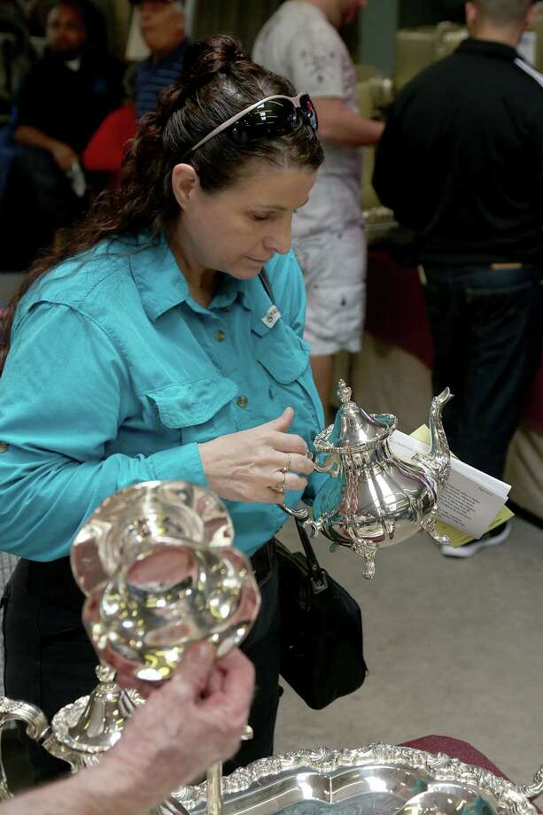 Lorraine Padden, from Katy, looks at a sterling silver six-piece tea set before the start of the fourth auction in Houston. Photo: Thomas B. Shea, The Houston Chronicle / © 2014 Thomas B. Shea