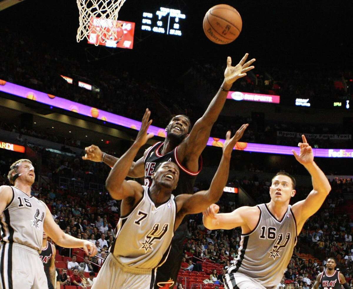 Miami Heat center Greg Oden fights for a rebound with San Antonio Spurs Othyus Jeffers, left, and San Antonio Spurs forward Aron Baynes, right, in the fourth quarter at the American Airlines Arena in Miami on Sunday, Jan. 26, 2014. (Hector Gabino/El Nuevo Herald/MCT)