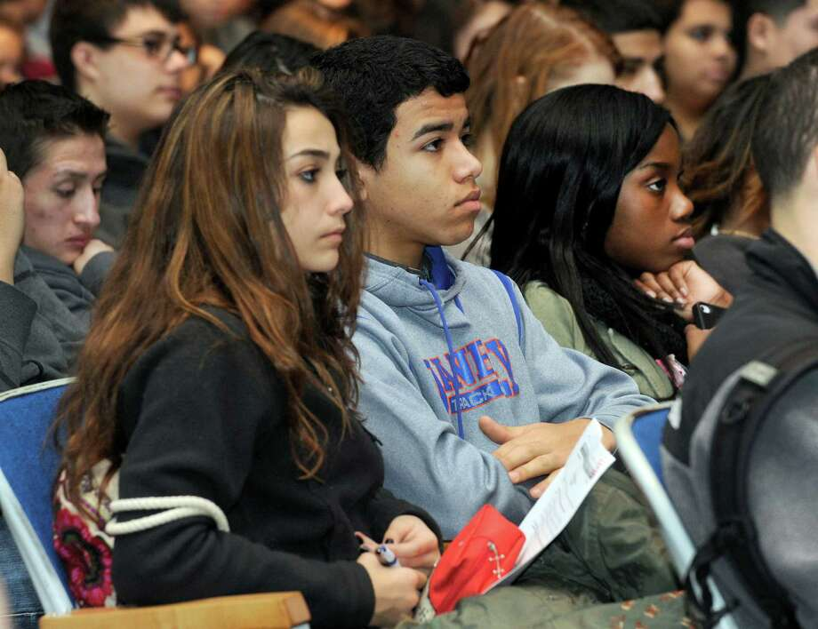 Listening to a talk about finacial literacy, and car insurance in particular, are from left, Gabriella Cardosa, 14, Marco Araujo, 16, and Eunique Dimmitt, 16. A project stemming from a business class at Danbury High School and developed into a DECA marketing class project, is presented to sophomores at the high school Thursday, January 16, 2014. Photo: Carol Kaliff / The News-Times