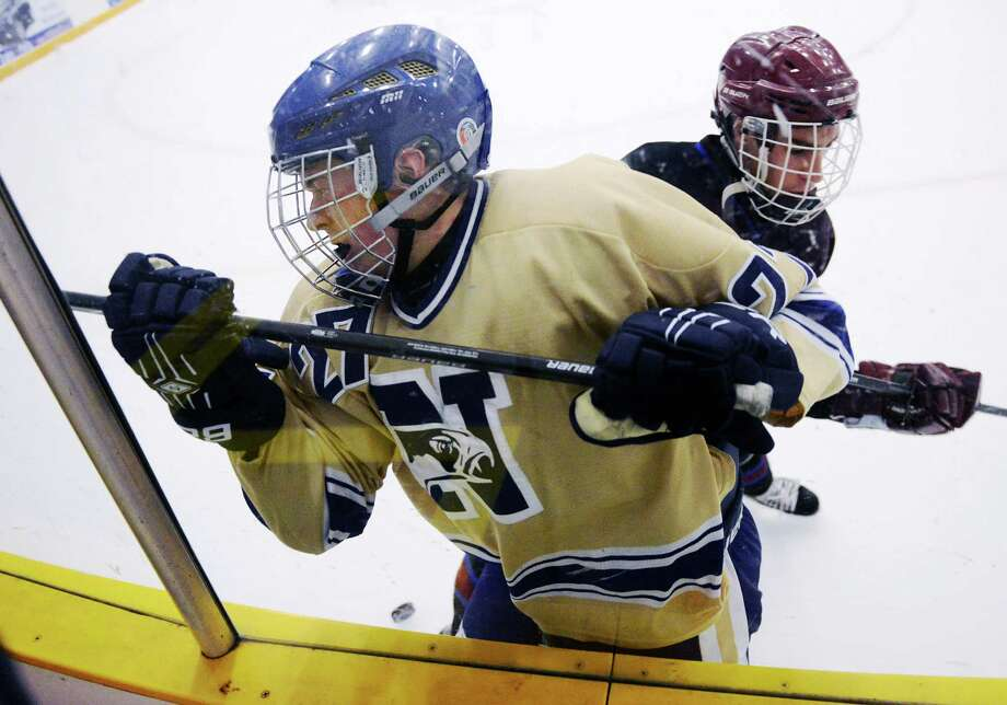 Newtown's David McKinnon (27) gets checked against the boards by Brookfield/Bethel/Danbury's Brennan Battochio in Newtown's 3-1 win over Brookfield/Bethel/Danbury in the high school hockey game at Danbury Arena in Danbury, Conn. on Saturday, Jan. 25, 2014. Photo: Tyler Sizemore / The News-Times