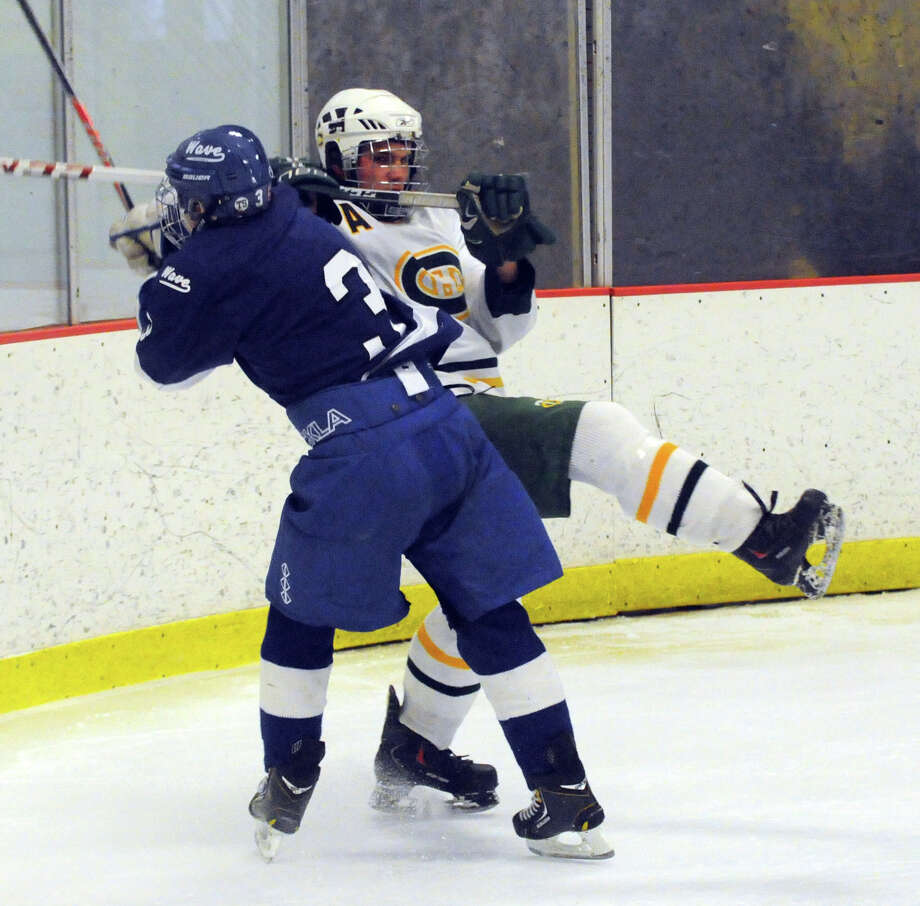 Darien's Thomas Watters collides with Trinity's Tyler Stenquist as Darien and Trinity Catholic High Schools face off in a boys hockey game at Terry Conners Rink in Stamford, Conn., Jan. 25, 2014. Photo: Keelin Daly / Stamford Advocate Freelance