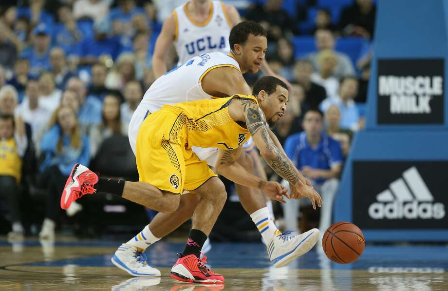 Cal's Justin Cobbs (foreground) and UCLA's Kyle Anderson reach for the ball in UCLA's victory. Photo: Jeff Gross, Getty Images
