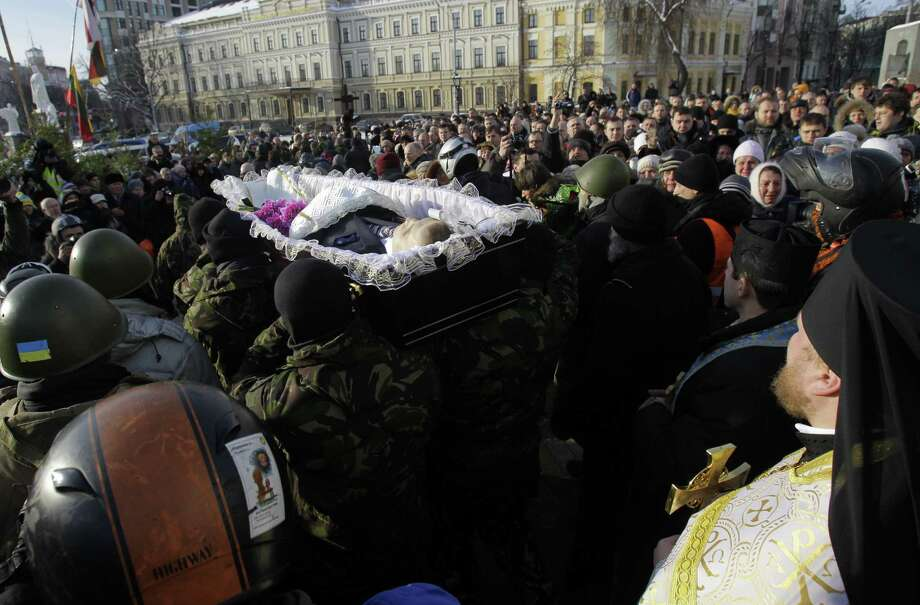 Protesters in Kiev, Ukraine, carry the coffin of Mikhail Zhiznevsky, 25, one of two protesters who died Wednesday of gunshot wounds. Ukraine has been mired in a political crisis the past two months. Photo: Darko Vojinovic / Associated Press / AP