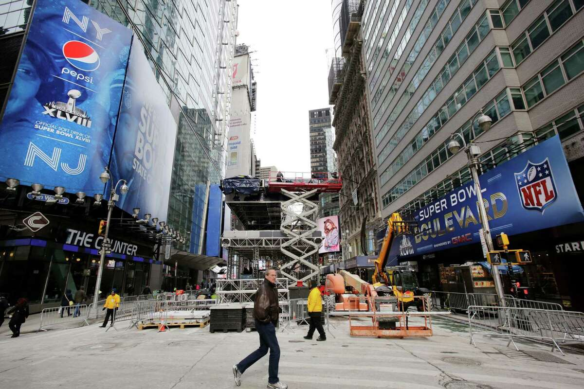 A pedestrian passes a soundstage under construction in New York's Times Square, Sunday, Jan. 26, 2014. A dozen blocks of Broadway, in the heart of Manhattan, will close to traffic for four days so the NFL can host a Super Bowl festival. The championship football game between the Denver Broncos and Seattle Seahawks is Sunday, Feb. 3 in East Rutherford, N.J. (AP Photo/Mark Lennihan) ORG XMIT: NYML104