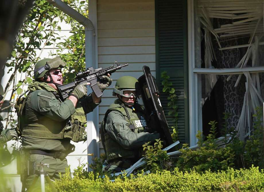 Waller County Sheriff's SWAT enters the home where suspect Gregory Robinson was in a stand off with police on Friday, Sept. 13, 2013, in Brookshire.  Gregory Robinson was found dead inside the home with a self inflicted wound. Robinson allegedly shot and killed his estranged wife Valerie Robinson earlier this morning at Tompkins High School. Photo: Mayra Beltran, Houston Chronicle / © 2013 Houston Chronicle