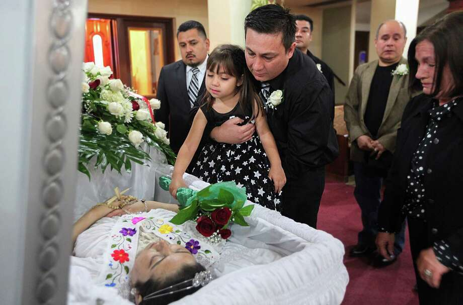Melissa Aguillon, 5, places flowers on her mother's casket while carried by father Luis Aguillon upon the conclusion of his wife's funeral mass at Christ the King Catholic Church on Jan. 9, 2013, in Houston. Maria Sanchez, Mexican immigrant who died on Sunday from a spinal tumor. Two years ago, upon learning that she was an illegal immigrant, the University of Texas Medical Branch ejected her from the hospital shortly before scheduled surgery on a spinal tumor. The tumor has slowly choked the life from her, gradually taking away control of her limbs and, recently, her eyesight. Scrawled on her discharge paper was the suggestion that she seek surgery in Mexico. Photo: Mayra Beltran, Houston Chronicle / © 2012 Houston Chronicle