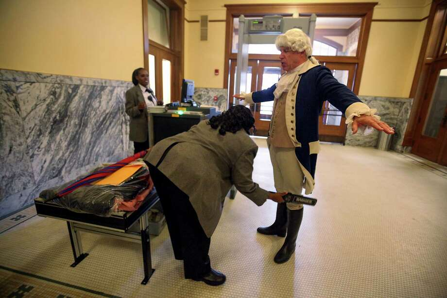 "Ron White, dressed as George Washington, is scanned by security before entering the historic Harris County Courthouse after the ""I Love Texas Courthouses"" campaign to raise awareness and show appreciation for Texas' historic courthouses on Monday, Feb. 18, 2013, in Houston. Photo: Mayra Beltran, Houston Chronicle / © 2013 Houston Chronicle"