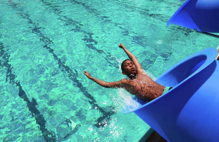 Rashad Coates, 11, enjoys the water slide on the last day that Houston pools open to the public at T.C.Jester Pool on Monday, Sept. 2, 2013, in Houston. Photo: Mayra Beltran, Houston Chronicle / © 2013 Houston Chronicle