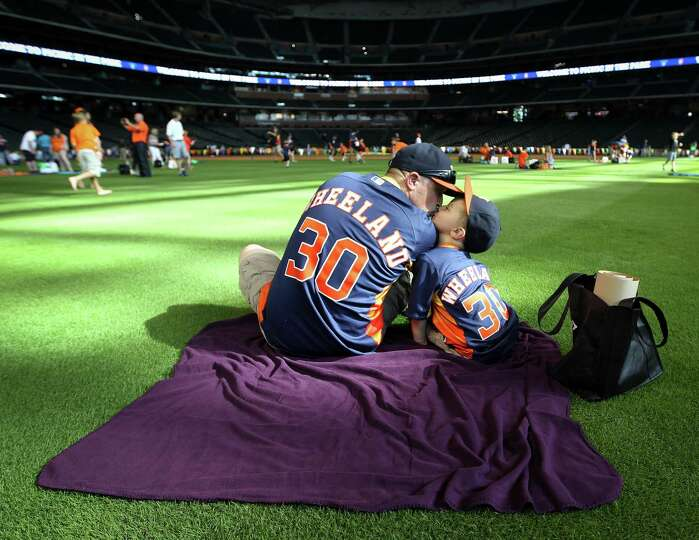 Dewayne Wheeland, left, kisses his son, Riley Wheeland, 4, in the outfield during the Houston Astros