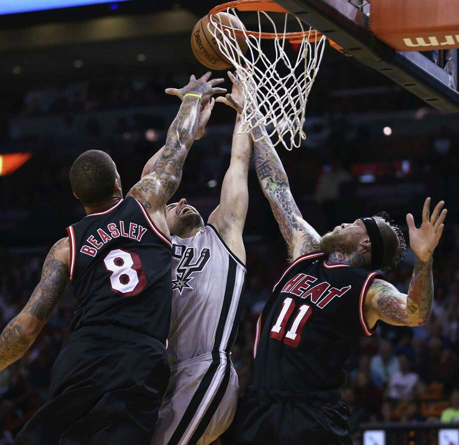Miami reserve forward Michael Beasley (left) and center Chris Andersen team up to block Spurs guard Manu Ginobili at the rim in the first half at AmericanAirlines Arena. Ginobili finished 1 of 7 from the floor for three points in Miami's 113-101 win. Photo: J. Pat Carter / Associated Press / AP