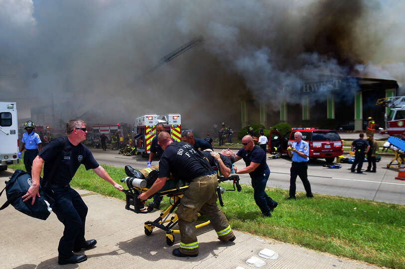 A firefighter is wheeled to an ambulance after fighting a 5-alarm blaze at the Southwest Inn on Horn
