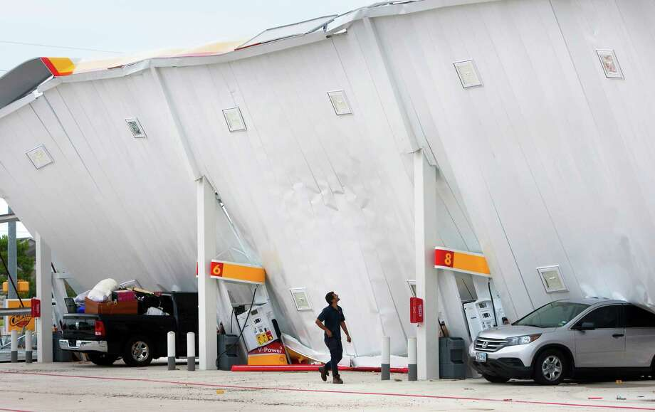 A man surveys the damage of a partial roof collapse at a shell gas station in the 16900 block of Tuckerton due to heavy rain and wind, Monday, July 15, 2013, in Houston. Authorities responded to the collapse late Sunday transporting one female patron by ambulance for precautions to Cy Fair Hospital. The collapse caused no other injuries. Photo: Cody Duty, Houston Chronicle / © 2013 Houston Chronicle