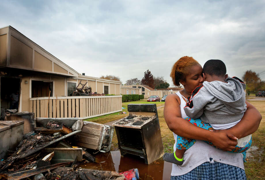 "Rolanda Gray holds her four-year-old son, Jemil Gray, as she looks at the rubble from an early morning fire outside their apartment at Huntington Village apartments Friday, Dec. 20, 2013, in Houston. Jemil woke his mom up after the fire started in their apartment giving her enough time to get him and his 17-year-old sister out of the home. ""We lost everything,"" she said, including Christmas presents. Photo: Cody Duty, Houston Chronicle / © 2013 Houston Chronicle"
