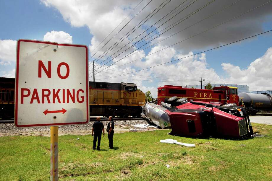 An 18-wheeler sits overturned sandwiched between two trains at a railroad crossing along Jacinto Port near S. Sheldon Rd., Tuesday, July 9, 2013, in Houston. The truck tried to beat an Eastbound train when the train collided with it pushing it into a parked, Westbound train spilling nearly 6,000 gallons of non-hazardous lubricant. The driver sustained no injuries. Photo: Cody Duty, Houston Chronicle / © 2013 Houston Chronicle