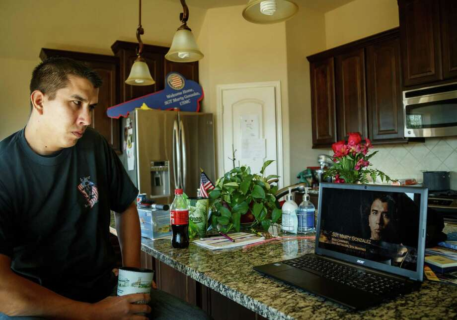 "Retired Marine Sgt. Marty Gonzalez watches a recording of himself on the Miltary Channel's Ultimate Warfare Episode: ""Fallujah: The Taking of Terror Central."" Photo: Michael Paulsen / Houston Chronicle / © 2014 Houston Chronicle"