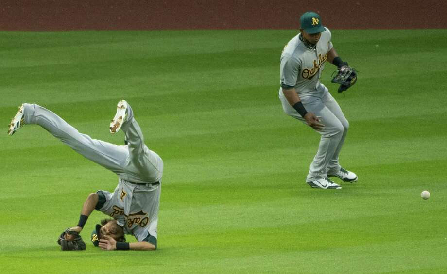 Oakland Athletics center fielder Coco Crisp tumbles upside-down as he tries to dive for a single by Houston Astros' Chris Carter in the first inning at Minute Maid Park on Friday, April 5, 2013, in Houston.  Oakland left fielder Yoenis Cespedes backs him up on the play. Photo: Smiley N. Pool, Houston Chronicle / © 2013  Smiley N. Pool