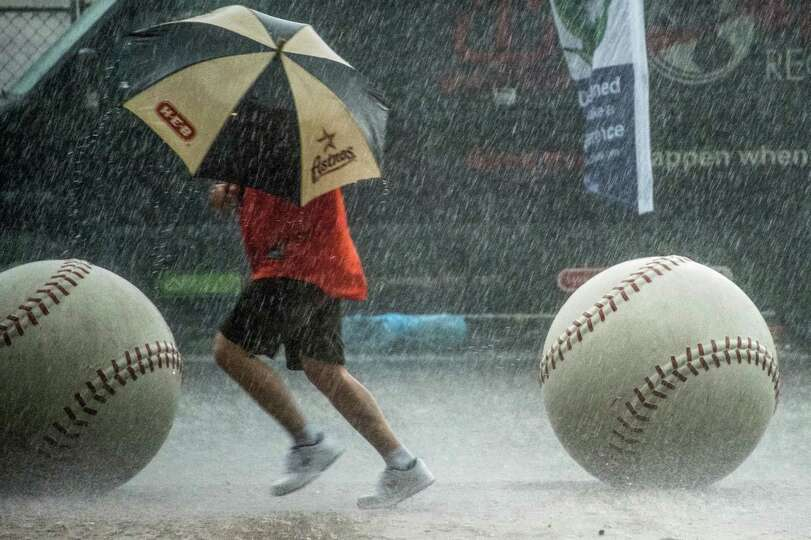 A Houston Astros fan runs for the stadium in a downpour before the Astros season opener against the