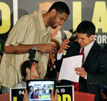 Spurs' Tim Duncan (left) jokes with Nicholas LaHood, who is running for district attorney, as Duncan's son Draven looks on Saturday Jan. 18, 2014 at the St. Paul Community Center. Photo: San Antonio Express-News / © 2014 San Antonio Express-News