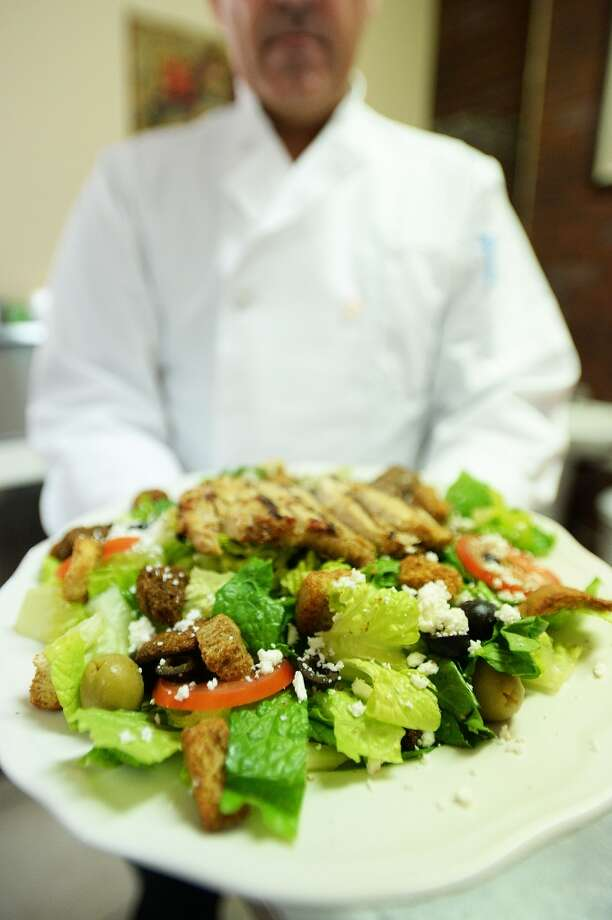 Owner and chef of County Line Diner Rex Harris holds a plate of grilled chicken greek salad that he has prepared Wednesday. Michael Rivera/@michaelrivera88    Photo Taken Wednesday, 01/15/14