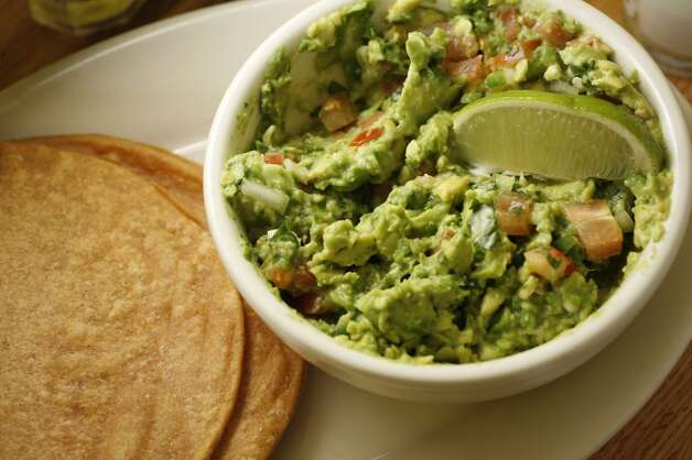 "Guacamole (wock-a-MOH-leh): A dip of mashed avocados, lemon or lime juice, and optional ingredients such as onions, tomatoes, chiles and other spices. Audio: Click here to hear the term ""Guacamole."" Photo: Craig Lee, The Chronicle"