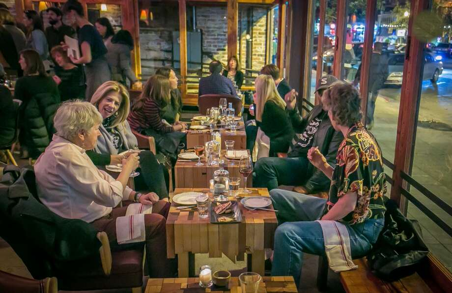 Diners enjoy dinner at the short tables at Penrose in Oakland. Photo: John Storey, Special To The Chronicle