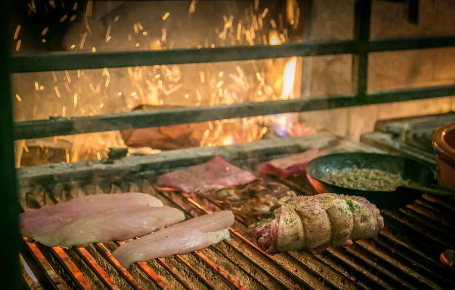 Meat and fish cooking on the grill at Penrose in Oakland. Photo: John Storey, Special To The Chronicle