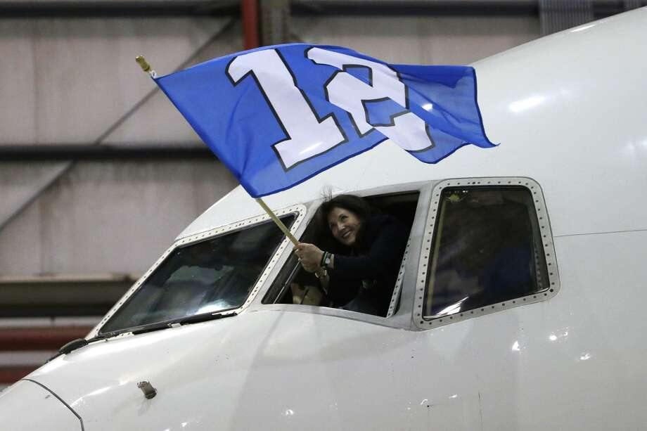 Hours later, the Seahawks arrived in New Jersey with fanfare. Delta flight attendant  Christi Turner waves the 12th Man flag on Sunday as the charter plane carrying the Seattle  Seahawks arrives at Newark Liberty International Airport for  the Super Bowl.  (AP Photo/Matt Slocum)