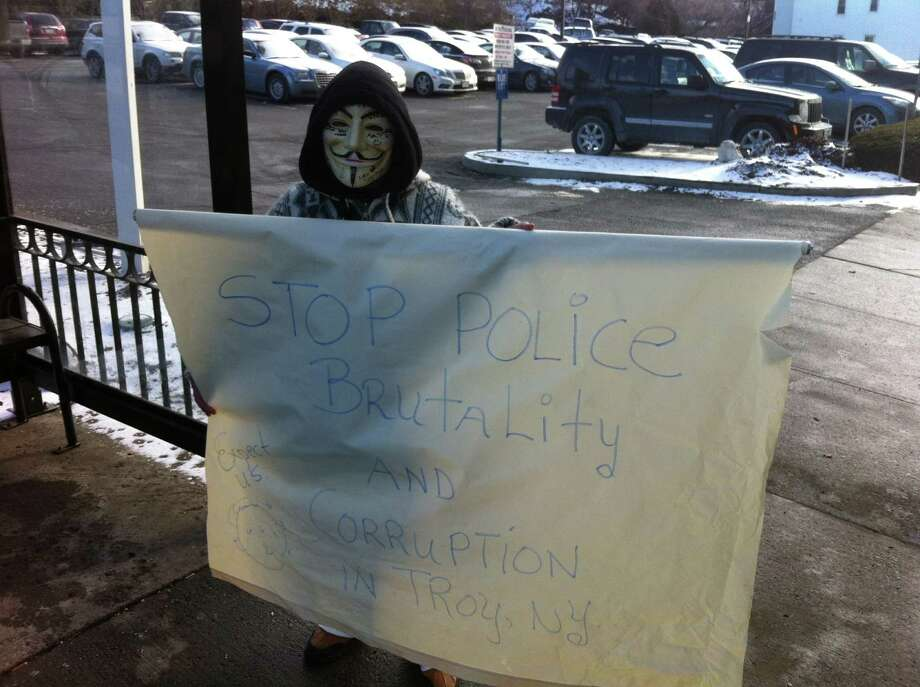 An anonymous protester holds up a sign outside Troy City Hall to decry police brutality. (Kenneth C. Crowe II / Times Union)