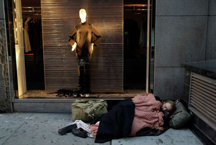 File photo shows a destitute man sleeping on the sidewalk under a holiday window at Blanc de Chine in New York. Photo: Mark Lennihan / AP