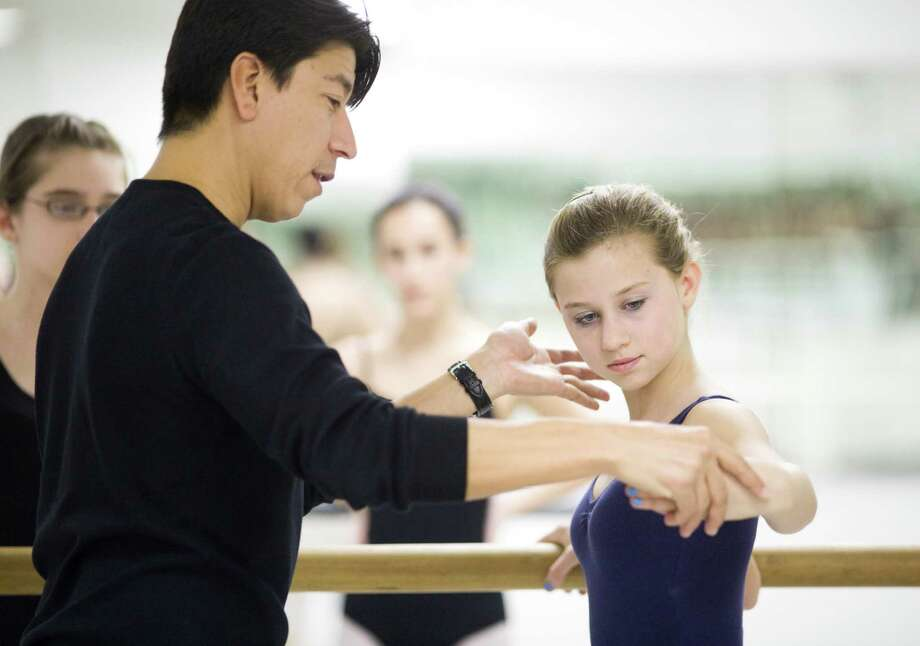 "Instructor Flavio Salazar, left, works with a dancer during a class at the Ballet School of Stamford in 2010. Salazar, a professsional ballet dancer who retired from performing in 2006, is featured in the documentary ""First Position,"" which will be presented at the Avon Theatre in Stamford, Conn., on Wednesday, Feb. 5, 2014. Photo: File Photo / Stamford Advocate File Photo"