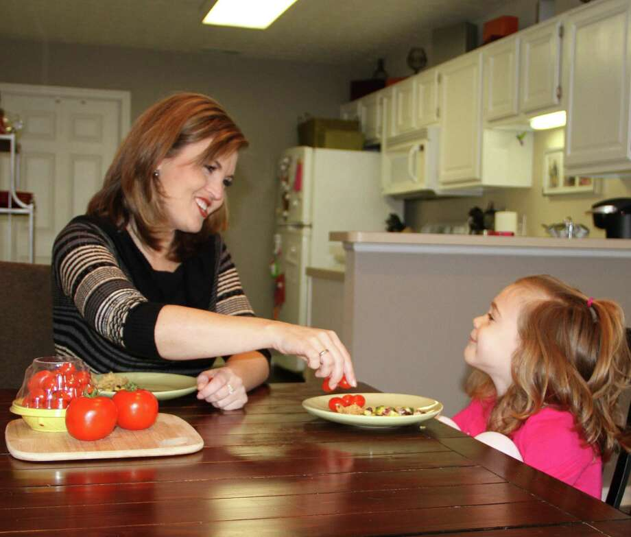 Tomato-hating Shannon McCormick serves one to her 4-year-old daughter, Sophie Chapman, who loves them. Photo: Associated Press / MediaSource