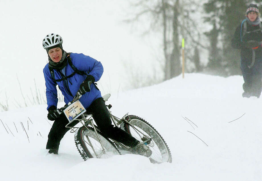 Kathy Evingson tries to ride her bike through the deep snow during the Little-Su 50K at Point Mackenzie near Knik, Alaska on Sunday Feb. 17, 2008.  The 31-mile trek across frozen rivers and snowy swamps, open to skiers, snowshoers and runners, it is often won by competitors using bicycles. (AP Photo/Robert DeBerry ) Photo: ROBERT DeBERRY, San Francisco Chronicle / AP