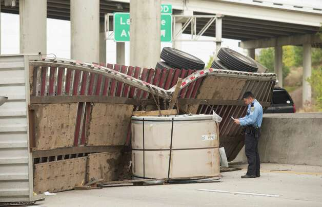 A Houston Police Officer works the scene of a big rig roll over on the southbound lanes of the east loop near the La Porte freeway on Monday, Jan. 27, 2014, in Houston. Photo: J. Patric Schneider, For The Chronicle / © 2014 Houston Chronicle