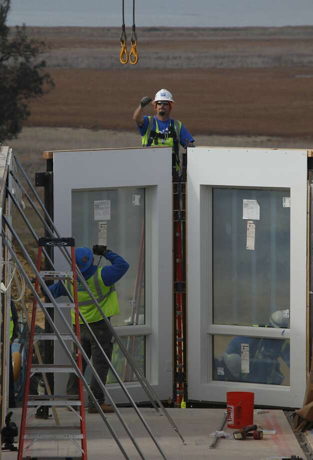 "Workers build the first of four houses on Mare Island in Vallejo that will serve as a ""design center"" for prefab-home builder Blu Homes. The center will allow prospective buyers to see Blu's work. Photo: Liz Hafalia, The Chronicle"