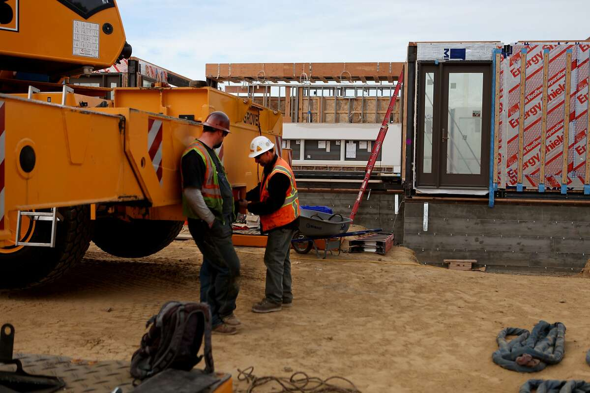 During their lunch break Jake Burns (left) the crane oiler and Steve Cooper (right) the crane operator, prepare to start operations again. The Blu Homes prefab home called the Breezehouse is delivered on a flatbed truck, lifted by a 550 ton crane and transformed into a home in only a few hours at Mare Island in Vallejo, Calf. on January 28, 2014.