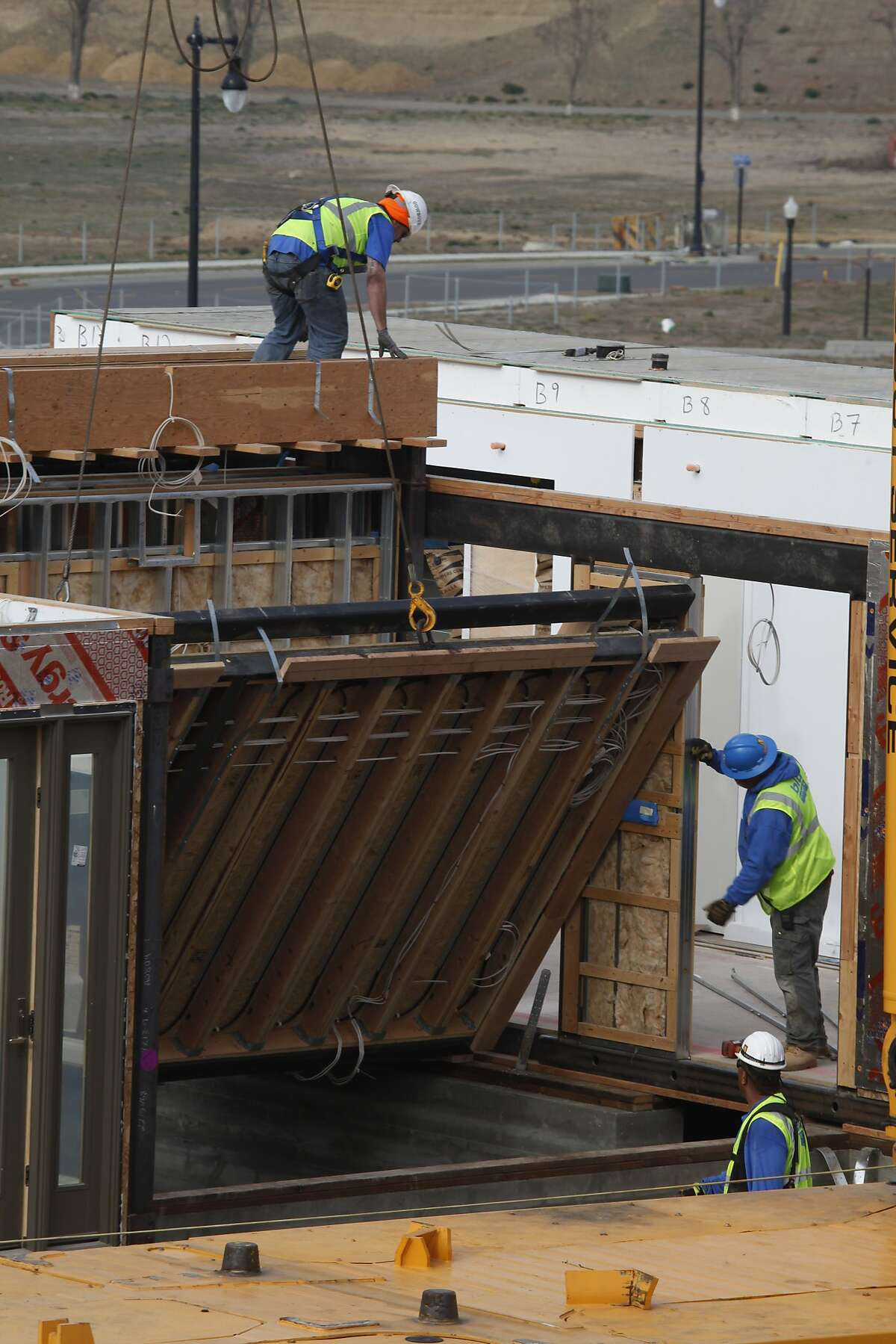 Construction works on a Blu Homes Design Center Breezehouse in Mare Island, Vallejo, Calif., as a floor folds out on Monday, January 27, 2014.