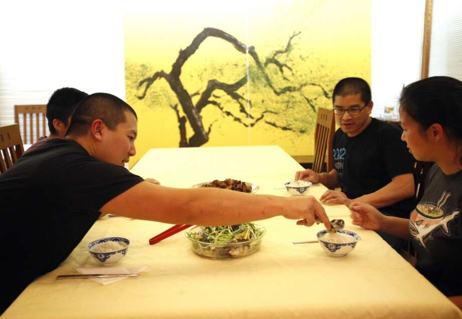 Jared Young, left, serves Melvina Lee and her husband Jeff Lee after cooking a traditional Chinese New Year feast at their home in Berkeley, Calif., on Friday, January 17, 2014. Photo: Special To The Chronicle