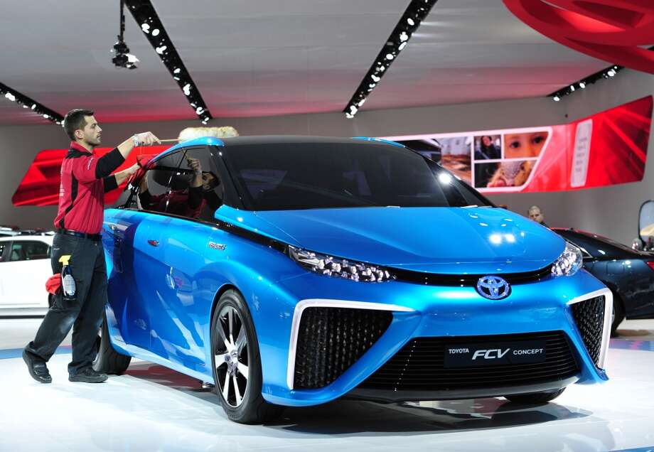 A worker cleans a 2015 Toyota hydrogen-fueled  FCV concept car on display during a press preview at the North American International Auto Show in Detroit, Michigan. (STAN HONDA/AFP/Getty Images) Photo: STAN HONDA, AFP/Getty Images