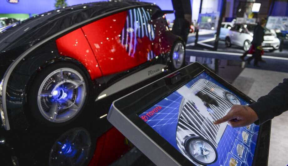 A car enthusiast scrolls through displays that are displayed onto the outer body of the Toyota FunVii concept car during the 2104 Washington Auto Show in Washington, D.C. (Photo by Ricky Carioti/The Washington Post via Getty Images) Photo: The Washington Post, The Washington Post/Getty Images