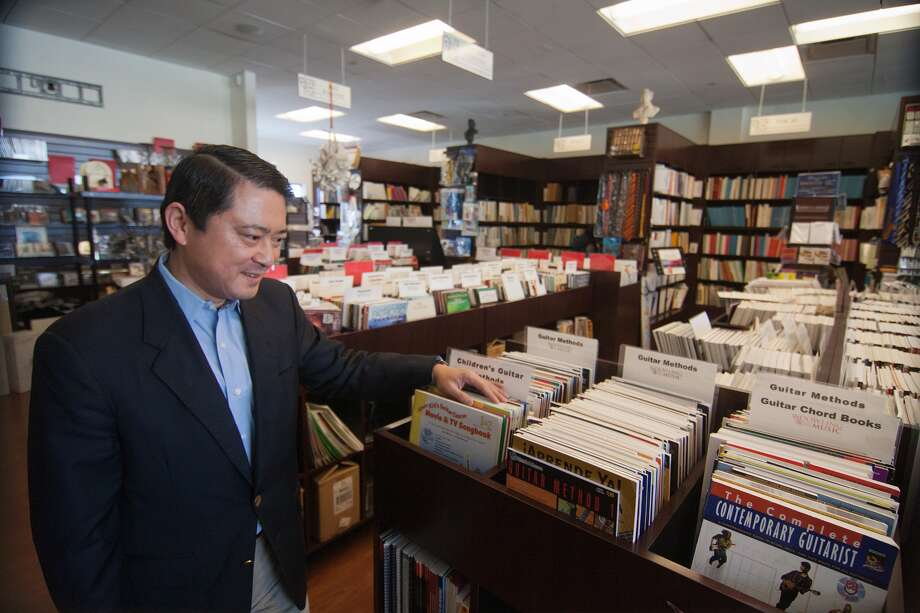 Dowling Music president and co-owner James Li reviews music books at the store, which is closing. Started in 1943 as Wadler-Kaplan Music Shop, the business offered a comprehensive range of sheet music. Photo: R. Clayton McKee, Freelance / © R. Clayton McKee